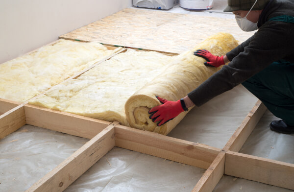 worker installing mineral wool insulation through Green Homes Grant